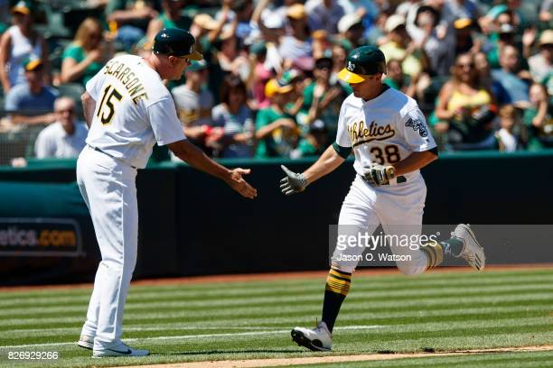 Jaycob Brugman of the Oakland Athletics is congratulated by third base coach Steve Scarsone after hitting a home run against the Minnesota Twins...
