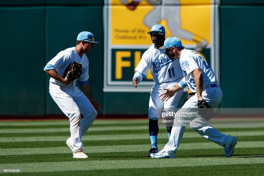 Jaycob Brugman #38 of the Oakland Athletics, Rajai Davis #11 and Matt Joyce #23 celebrate after the game against the New York Yankees at the Oakland Coliseum on June 17, 2017 in Oakland, California. The Oakland Athletics defeated the New York Yankees 5-2. Players and umpires are wearing blue to celebrate Father's Day weekend and support prostrate cancer awareness.