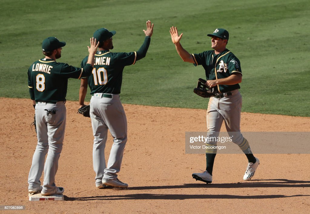 Jaycob Brugman #38 of the Oakland Athletics, right, looks to give teammate Marcus Semien #10 a high-five to celebrate their win in their MLB game against the Los Angeles Angels of Anaheim at Angel Stadium of Anaheim on August 6, 2017 in Anaheim, California. The Athletics defeated the Angels 11-10.