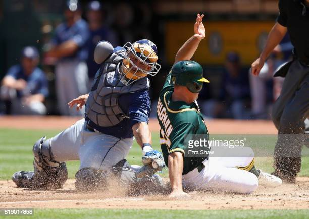 Jaycob Brugman of the Oakland Athletics safely slides past Wilson Ramos of the Tampa Bay Rays to score in the fifth inning at Oakland Alameda...