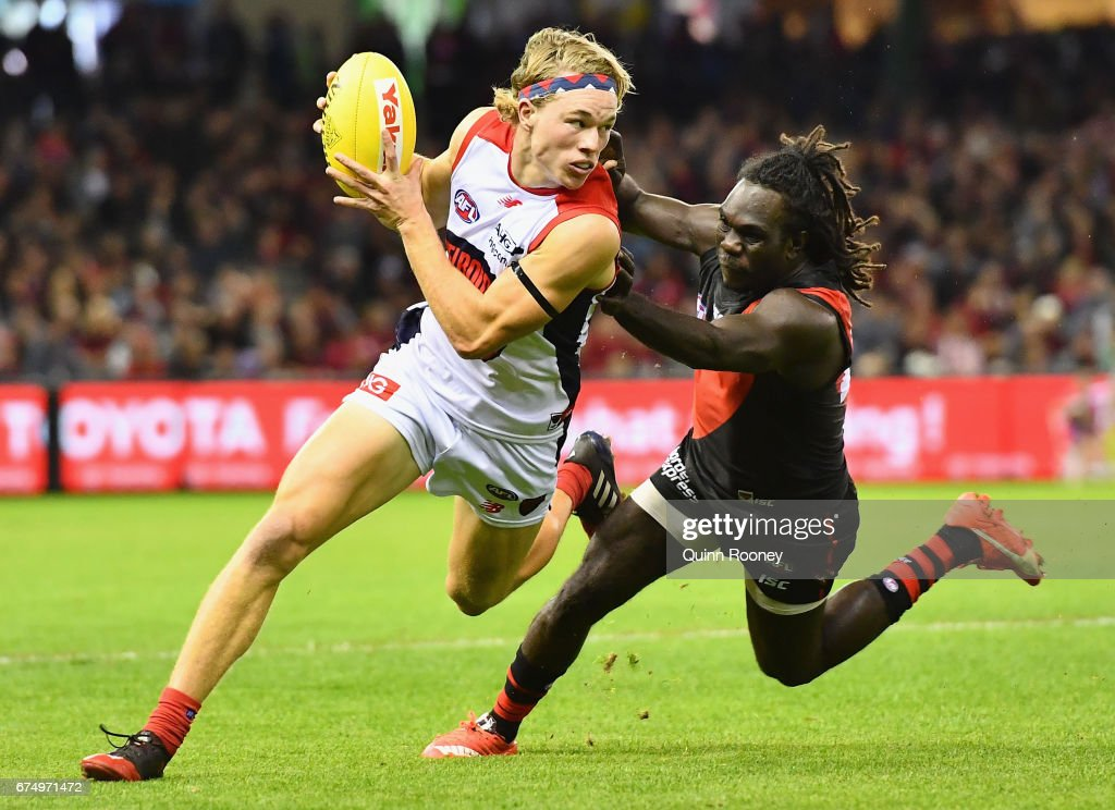 Jayden Hunt of the Demons breaks free of a tackle by Anthony McDonald-Tipungwuti of the Bombers during the round six AFL match between the Essendon Bombers and the Melbourne Demons at Etihad Stadium on April 30, 2017 in Melbourne, Australia.
