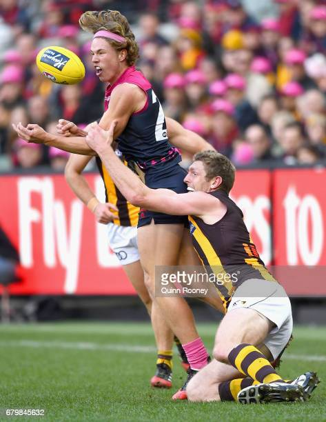 Jayden Hunt of the Demons handballs whilst being tackled Ben McEvoy of the Hawks during the round seven AFL match between the Melbourne Demons and...