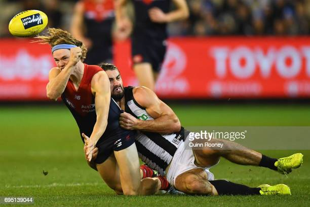 Jayden Hunt of the Demons handballs whilst being tackled by Brodie Grundy of the Magpies during the round 12 AFL match between the Melbourne Demons...