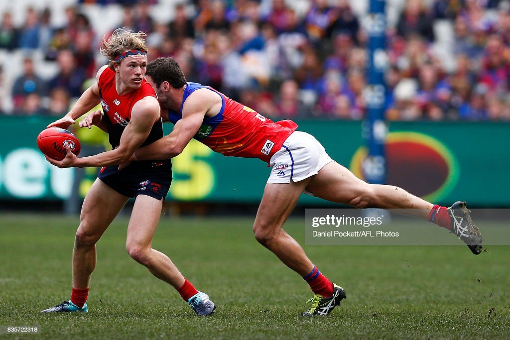 Jayden Hunt of the Demons handpasses the ball whilst being tackled by Michael Close of the Lions during the round 22 AFL match between the Melbourne Demons and the Brisbane Lions at Melbourne Cricket Ground on August 20, 2017 in Melbourne, Australia.