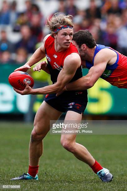 Jayden Hunt of the Demons handpasses the ball whilst being tackled by Michael Close of the Lions during the round 22 AFL match between the Melbourne...