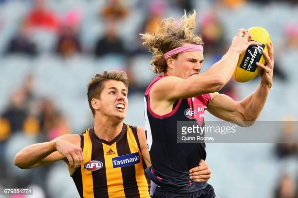 Jayden Hunt of the Demons marks infront of Ryan Burton of the Hawks during the round seven AFL match between the Melbourne Demons and the Hawthorn...