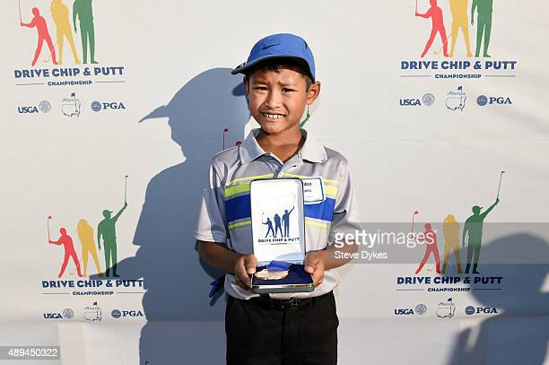 Jayden Lizama poses with his medal after winning the Chipping competition in the Boys 79 yr old division during the Drive Chip and Putt regional...