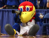 Jayhawk the mascot for the Kansas Jayhawks takes pictures with a camera from the photographer row against the Dayton Flyers during the second round...