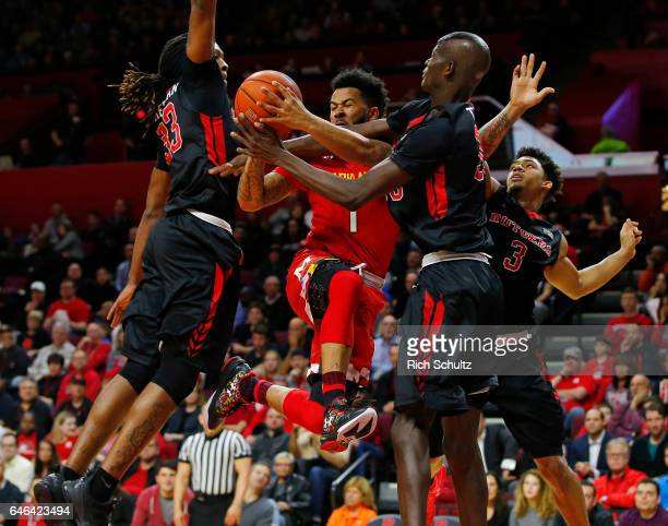 Jaylen Brantley of the Maryland Terrapins attempts a shot between Deshawn Freeman Issa Thiam and Corey Sanders of the Rutgers Scarlet Knights during...