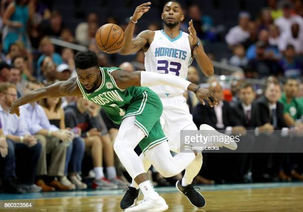 Jaylen Brown of the Boston Celtics goes after a loose ball against Terry Henderson of the Charlotte Hornets during their game at Spectrum Center on...