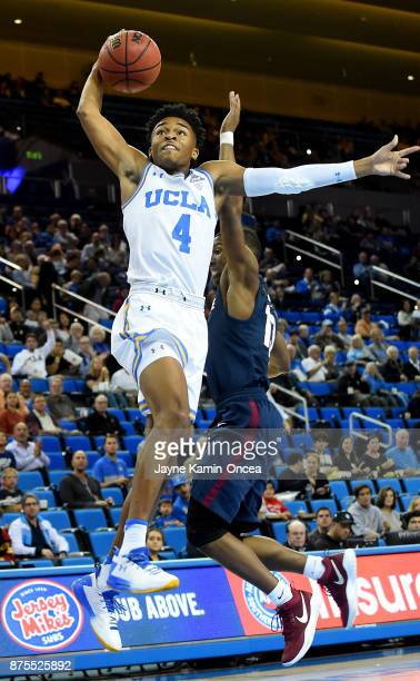 Jaylen Hands of the UCLA Bruins gets past the defense of Donte Wright of the South Carolina State Bulldogs as he dunks the ball in the first half of...