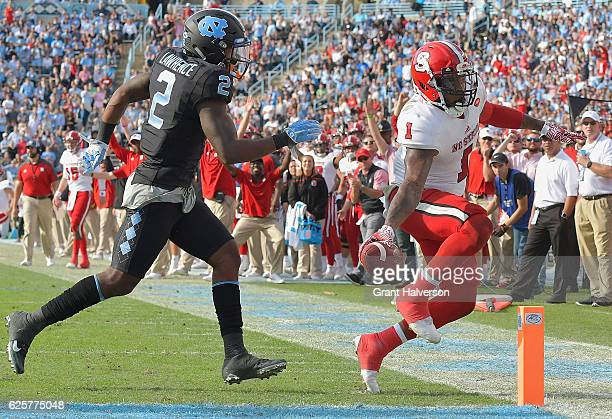 Jaylen Samuels of the North Carolina State Wolfpack scores a touchdown against Des Lawrence of the North Carolina Tar Heels during their game at...