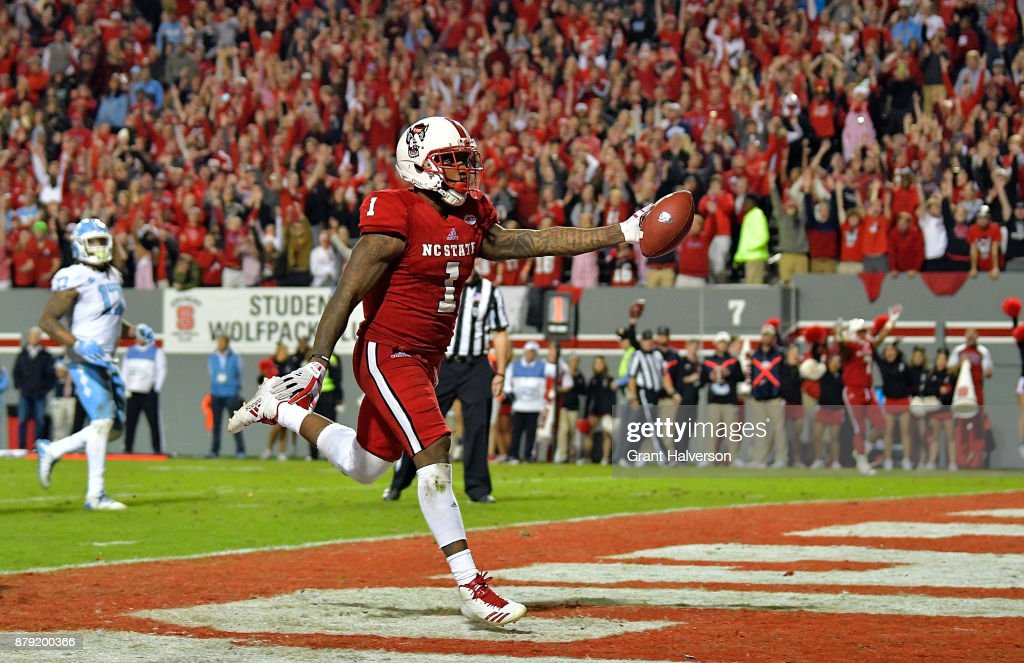 Jaylen Samuels #1 of the North Carolina State Wolfpack scores the game-clinching touchdown late in the fourth quarter of their game against the North Carolina Tar Heels at Carter Finley Stadium on November 25, 2017 in Raleigh, North Carolina. North Carolina State won 33-21.