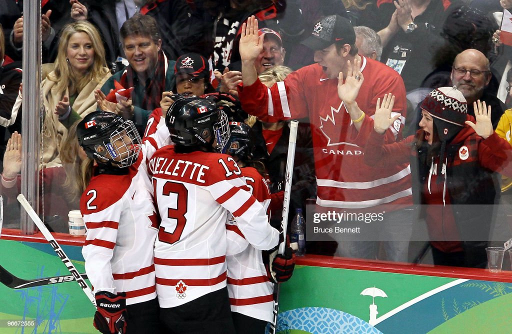 <a gi-track='captionPersonalityLinkClicked' href=/galleries/search?phrase=Jayna+Hefford&family=editorial&specificpeople=722132 ng-click='$event.stopPropagation()'>Jayna Hefford</a> of Canada (against glass, partially visible) is hugged by teammates <a gi-track='captionPersonalityLinkClicked' href=/galleries/search?phrase=Caroline+Ouellette&family=editorial&specificpeople=722185 ng-click='$event.stopPropagation()'>Caroline Ouellette</a> and Meghan Agosta after she scored in the third period against Slovakia during their women's ice hockey preliminary game at Canada Hockey Place on February 13, 2010 in Vancouver, Canada. Canada won the game by a score of 18-0.