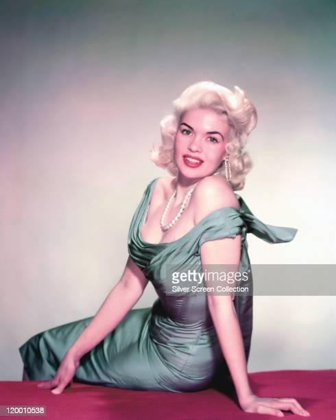 Jayne Mansfield US actress wearing a blue dress while sitting on a red surface in a studio portrait against a white background circa 1955