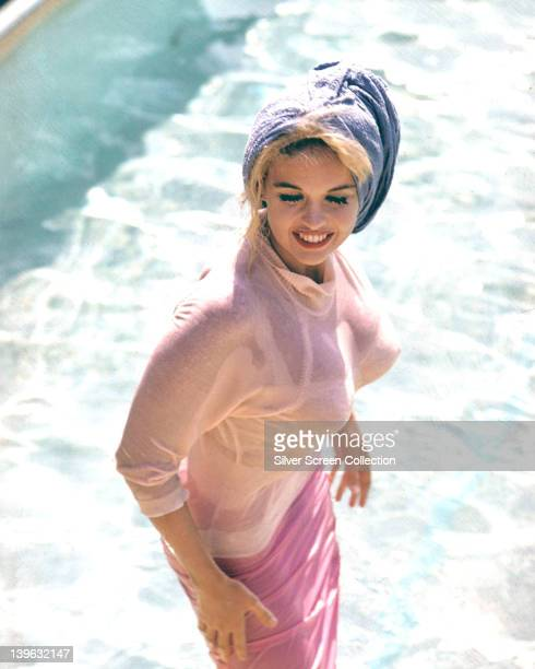 Jayne Mansfield US actress wearing a light pink jumper and a pink skirt with a lilac towel wrapped around her head with the sea in the background...