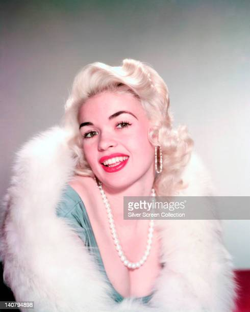 Jayne Mansfield US actress wearing a pearl necklace and a white fur wrap in a studio portrait circa 1960