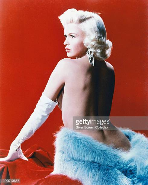 Jayne Mansfield US actress wearing long white gloves with a length of blue fur wrapped around her waist in a studio portrait against a red background...