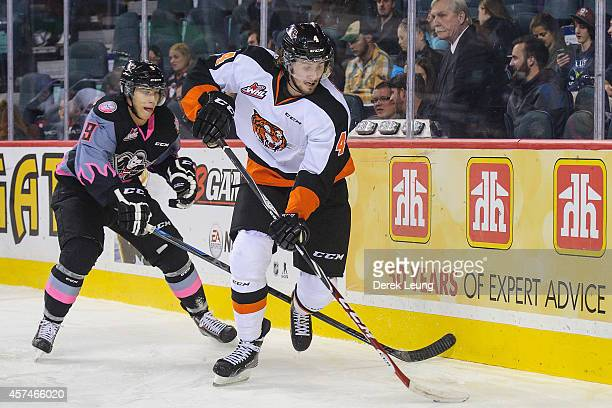 Jaynen Rissling of the Calgary Hitmen chases Cale Fleury of the Medicine Hat Tigers during a WHL game at Scotiabank Saddledome on October 18 2014 in...