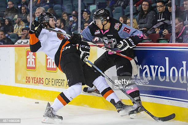 Jaynen Rissling of the Calgary Hitmen checks Cale Fleury of the Medicine Hat Tigers during a WHL game at Scotiabank Saddledome on October 18 2014 in...
