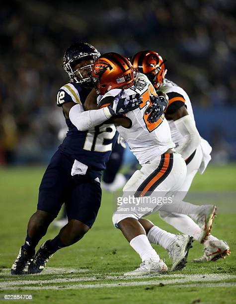 Jayon Brown of the UCLA Bruins tackles Artavis Pierce of the Oregon State Beavers during the first half of a game at The Rose Bowl on November 12...
