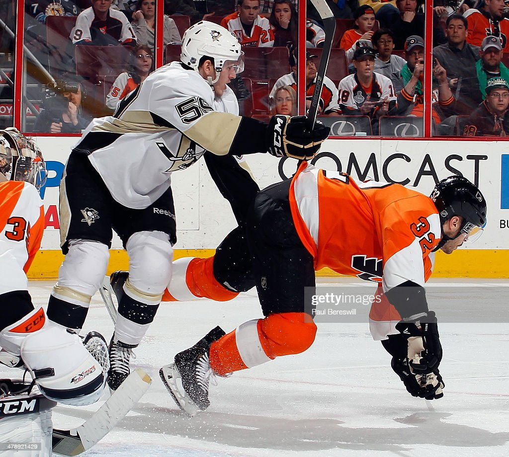 Jayson Megna #59 of the Pittsburgh Penguins checks Mark Streit #32 of the Philadelphia Flyers in the third period of an NHL hockey game at Wells Fargo Center on March 15, 2014 in Philadelphia, Pennsylvania.