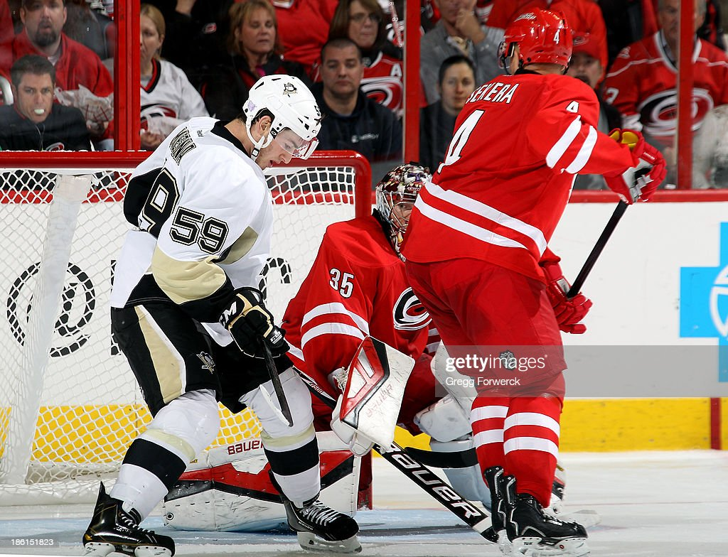 Jayson Megna #59 of the Pittsburgh Penguins creates traffic behind Justin Peters #35 and Andrej Sekera #4 of the Carolina Hurricanes just prior to scoring his first NHL goal at PNC Arena on October 28, 2013 in Raleigh, North Carolina.