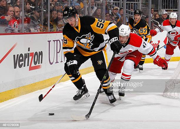 Jayson Megna of the Pittsburgh Penguins moves the puck in front of Michal Jordan of the Carolina Hurricanes at Consol Energy Center on December 31...