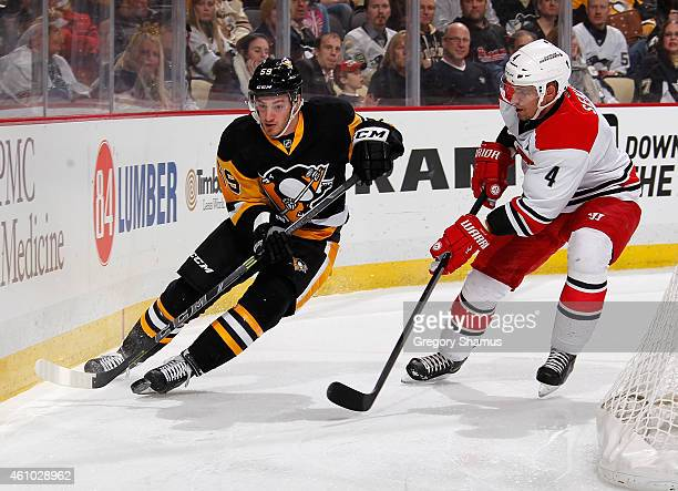 Jayson Megna of the Pittsburgh Penguins skates for the loose puck alongside Andrej Sekera of the Carolina Hurricanes at Consol Energy Center on...