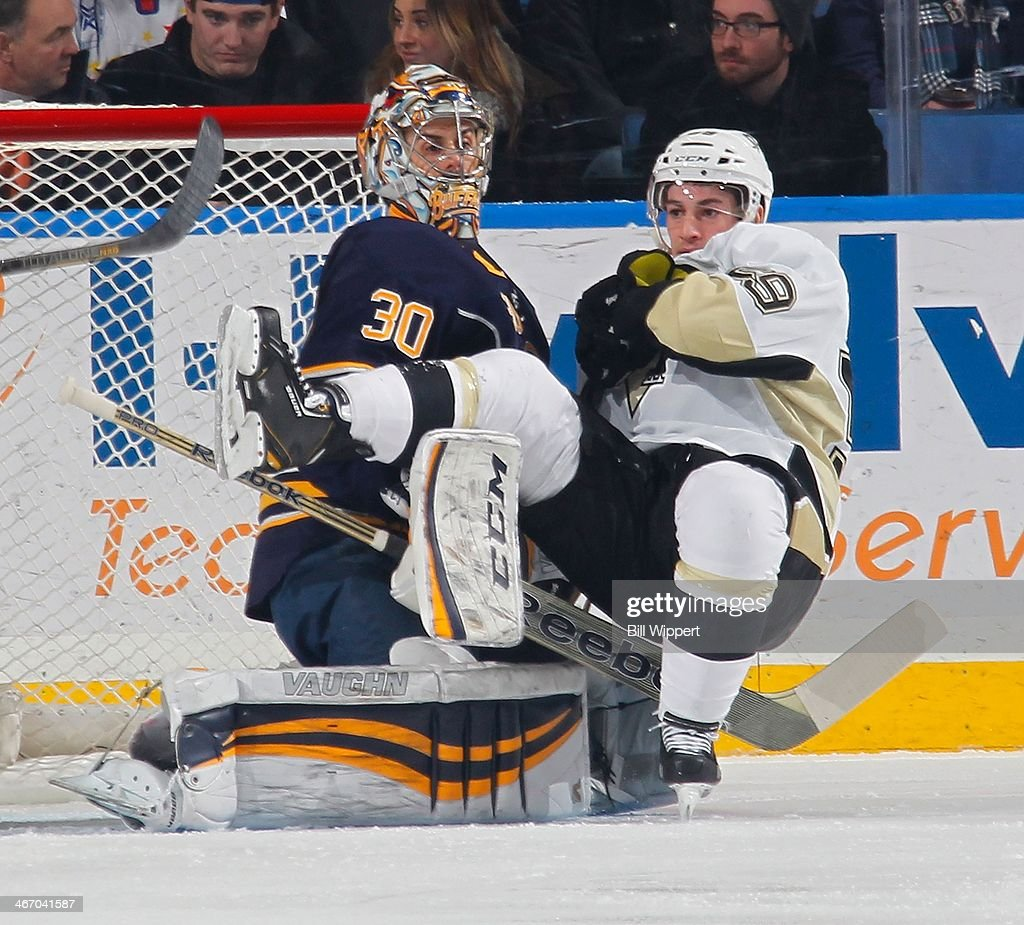Jayson Megna #59 of the Pittsburgh Penguins tumbles over Ryan Miller #30 of the Buffalo Sabres on February 5, 2014 at the First Niagara Center in Buffalo, New York.