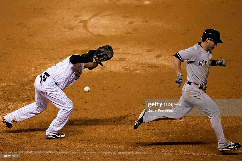 Jayson Nix #17 of the New York Yankees strides past first baseman Todd Helton #17 of the Colorado Rockies after Helton couldn't control the ball that was ruled an infield single during the ninth inning at Coors Field on May 7, 2013 in Denver, Colorado. The Rockies defeated the Yankees 2-0.
