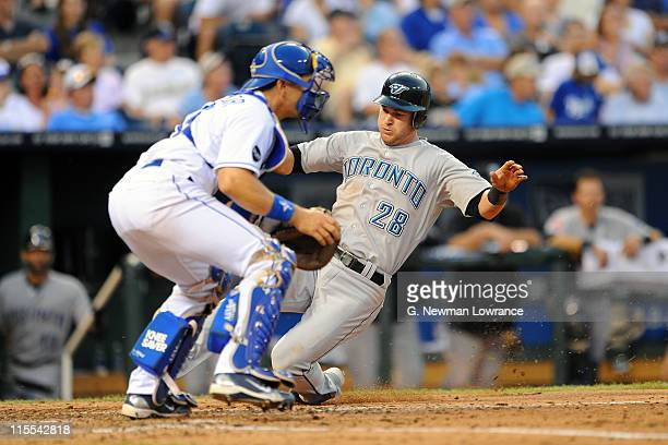 Jayson Nix of the Toronto Blue Jays slides in to score a run in the fifth inning as Matt Treanor of Kansas City Royals awaits the throw at Kauffman...