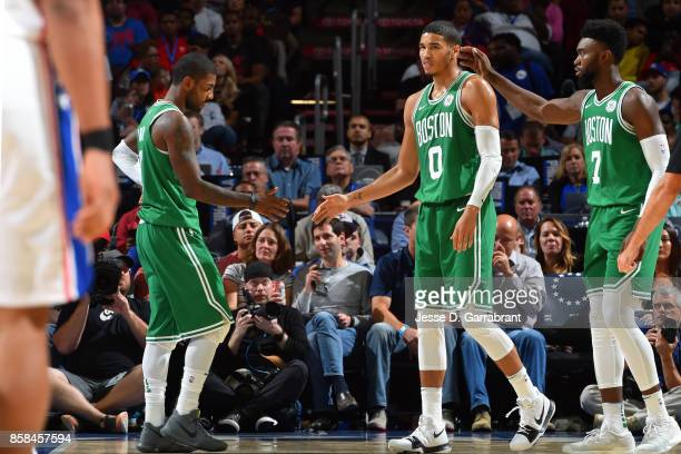 Jayson Tatum and Kyrie Irving of the Boston Celtics high five each other during the game against the Philadelphia 76ers during a preseason on October...