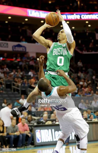 Jayson Tatum of the Boston Celtics drives to the basket against Kemba Walker of the Charlotte Hornets during their game at Spectrum Center on October...
