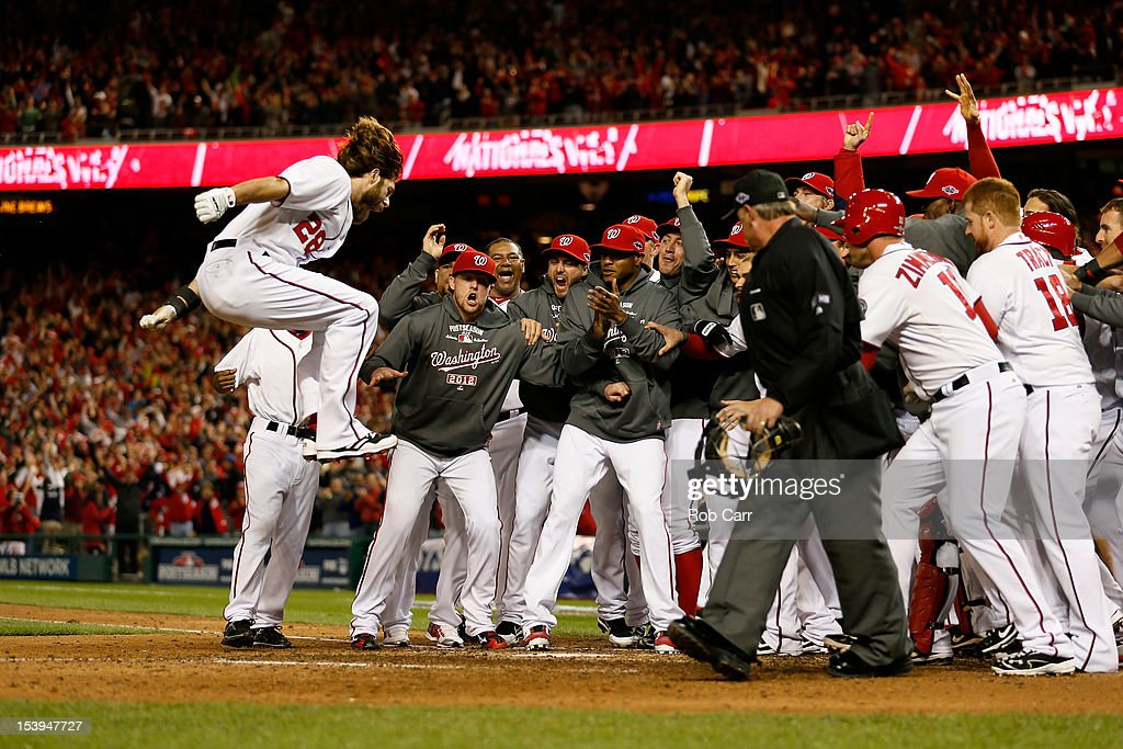 Jayson Werth (L) #28 of the Washington Nationals celebrates with his teammates as he jumps on home plate to score on his solo game-winning walk-off home run in the bottom of the ninth inning against the St. Louis Cardinals during Game Four of the National League Division Series at Nationals Park on October 11, 2012 in Washington, DC.