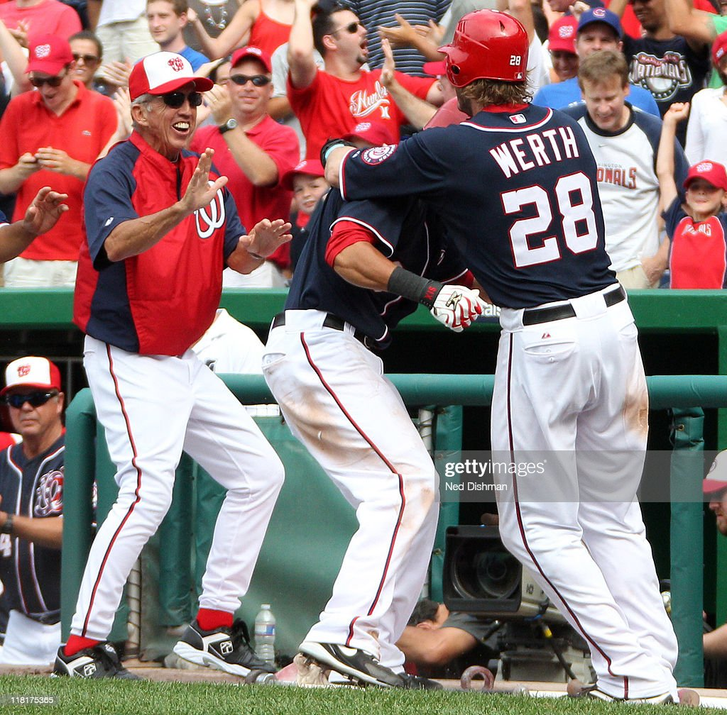 Jayson Werth and Ian Desmond and head coach Davey Johnson of the Washington Nationals celebrate after scoring the winning run on a wild pitch in the...