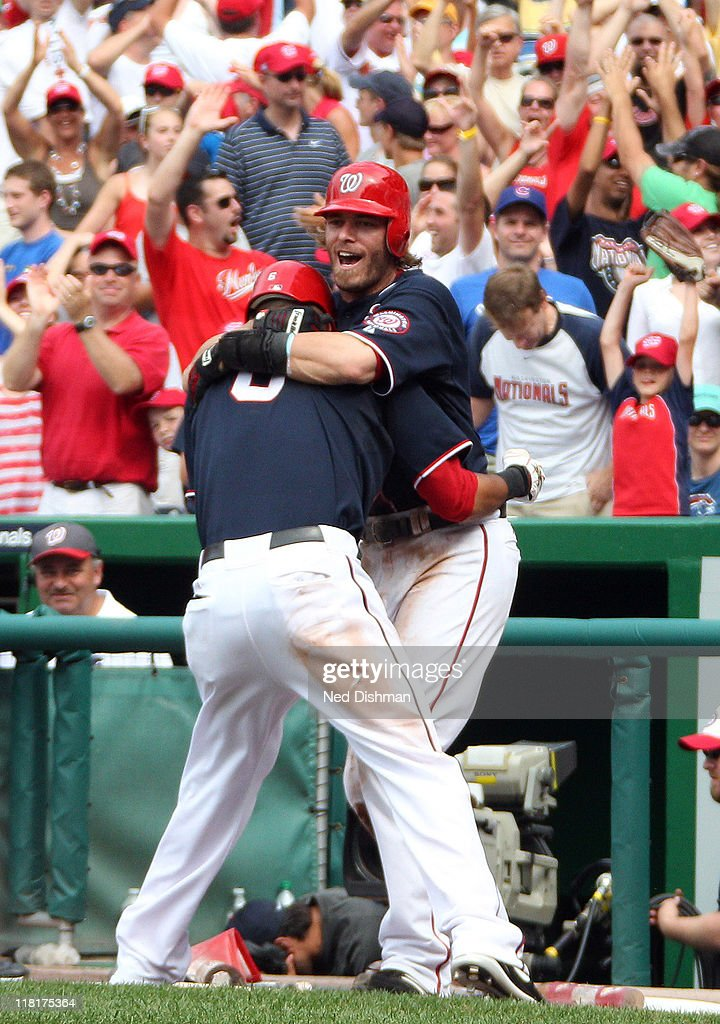 Jayson Werth and Ian Desmond of the Washington Nationals celebrate after scoring the winning run on a wild pitch in the tenth inning during a game...