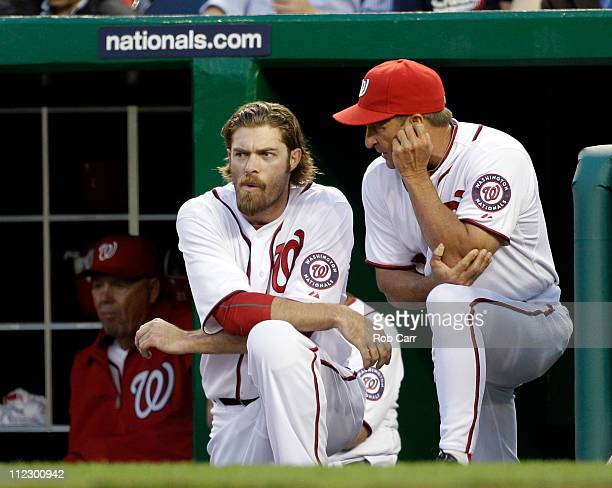 Jayson Werth and manager Jim Riggleman of the Washington Nationals talk in the dugout during their game against the Philadelphia Phillies at...