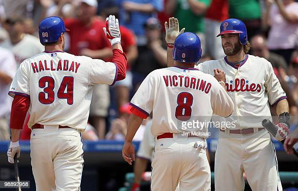 Jayson Werth of the Philadelphia Phillies congratultaes teammates Roy Halladay and Shane Victorino after they scored in the second inning against the...