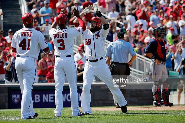 Jayson Werth of the Washington Nationals celebrates with Michael Taylor and Joe Ross after hitting a three RBI home run against the Atlanta Braves in...