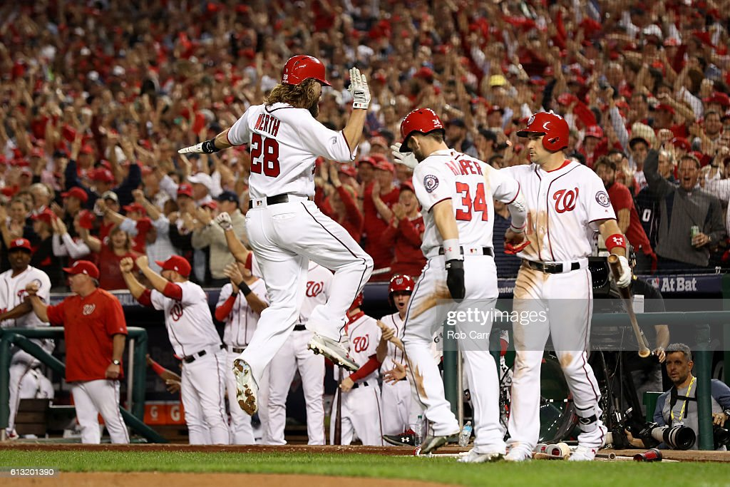 Jayson Werth #28 of the Washington Nationals celebrates with teammates Bryce Harper #34 and Ryan Zimmerman #11 after scoring off of a two run RBI single hit by Anthony Rendon #6 (not pictured) against the Los Angeles Dodgers during the third inning in game one of the National League Division Series at Nationals Park on October 7, 2016 in Washington, DC.