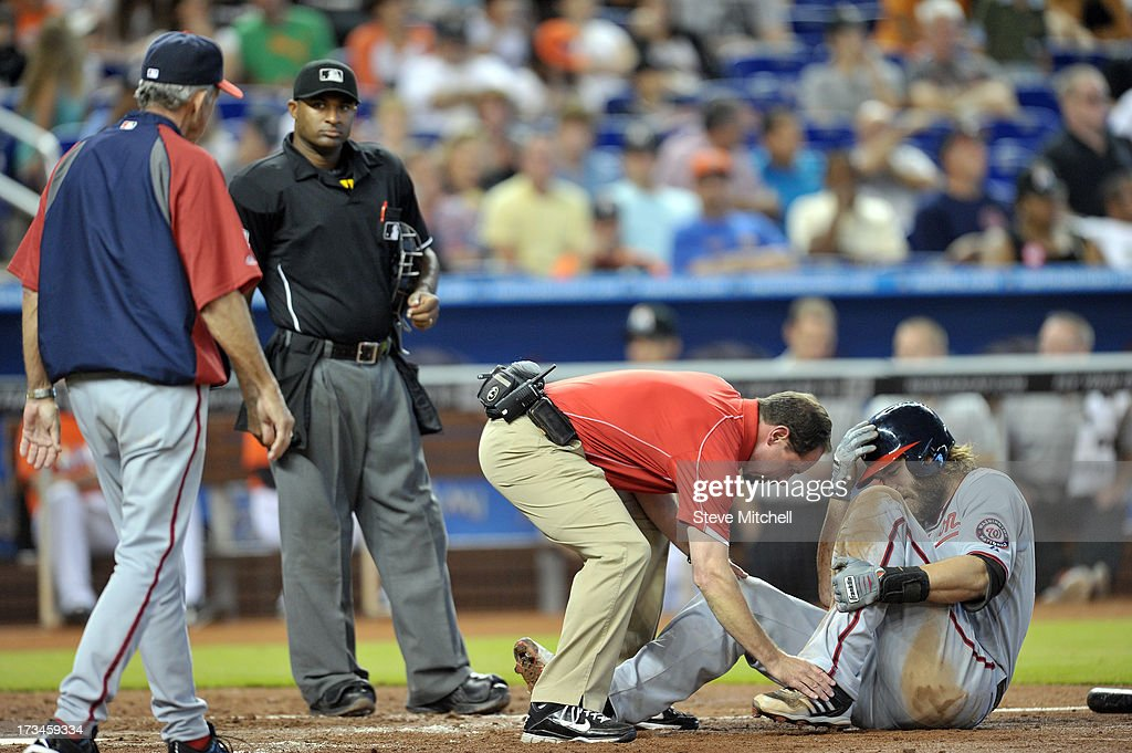 Jayson Werth #28 of the Washington Nationals seeks medical attention after fouling off a pitch during the sixth inning against the Miami Marlins at Marlins Park on July 14, 2013 in Miami, Florida.