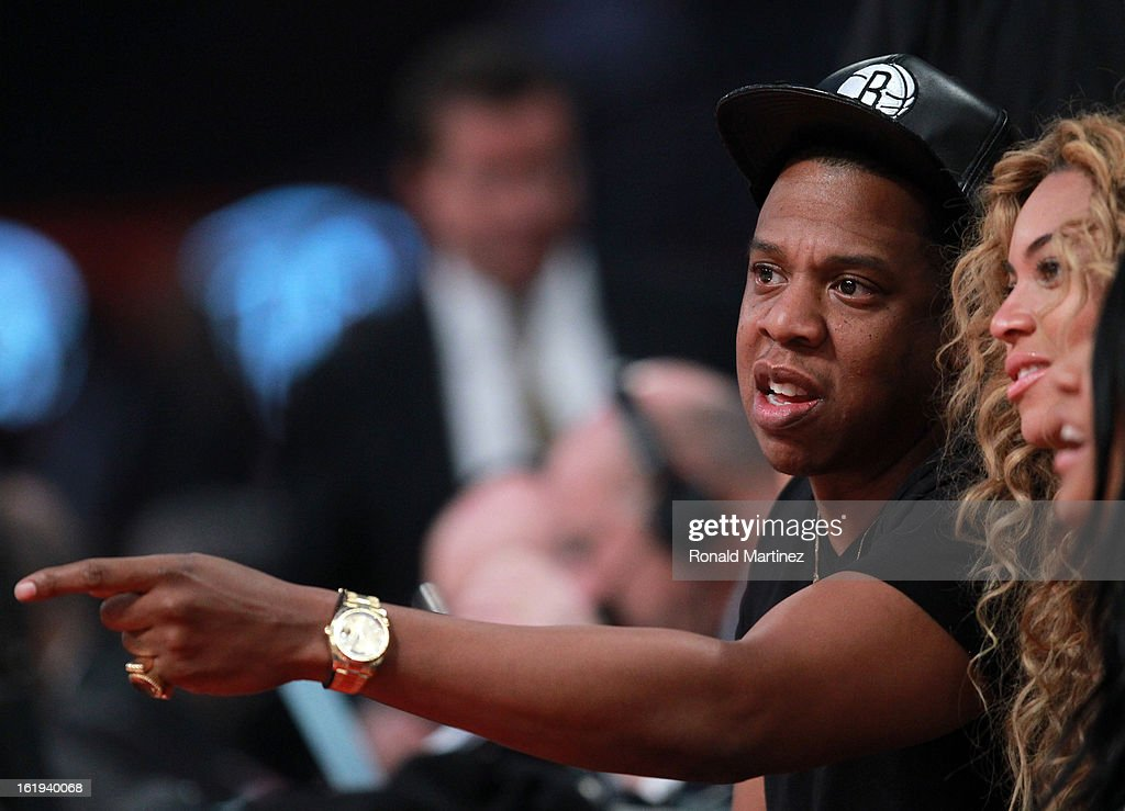 Jay-Z points as Beyonce looks on during the 2013 NBA All-Star game at the Toyota Center on February 17, 2013 in Houston, Texas.