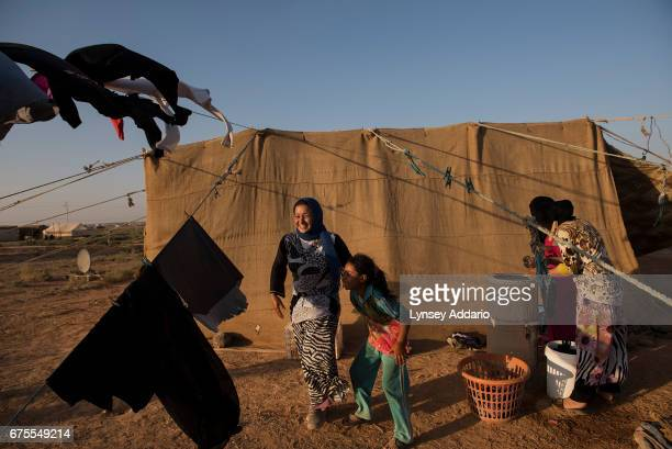 Jazia center a Syrian refugee from Hama laughs with her little sister as they wash clothes outside of her family's tent in a small camp for seasonal...