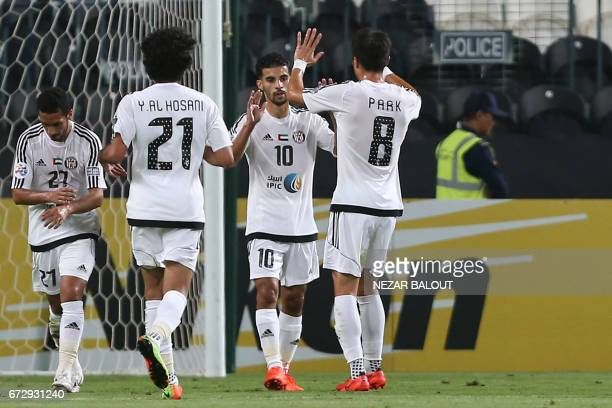 Jazira's Moroccan midfielder Mbark Boussoufa is congratulated by teammates after scoring a penalty during their AFC Champions League group B football...