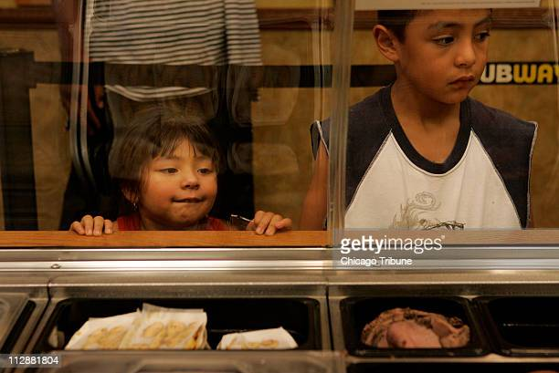 Jazmin Gonzalez and her brother Emmannuel Gonzalez watch as their sandwiches are made at a Subway in Elgin Illinois Monday August 4 2008 Though...
