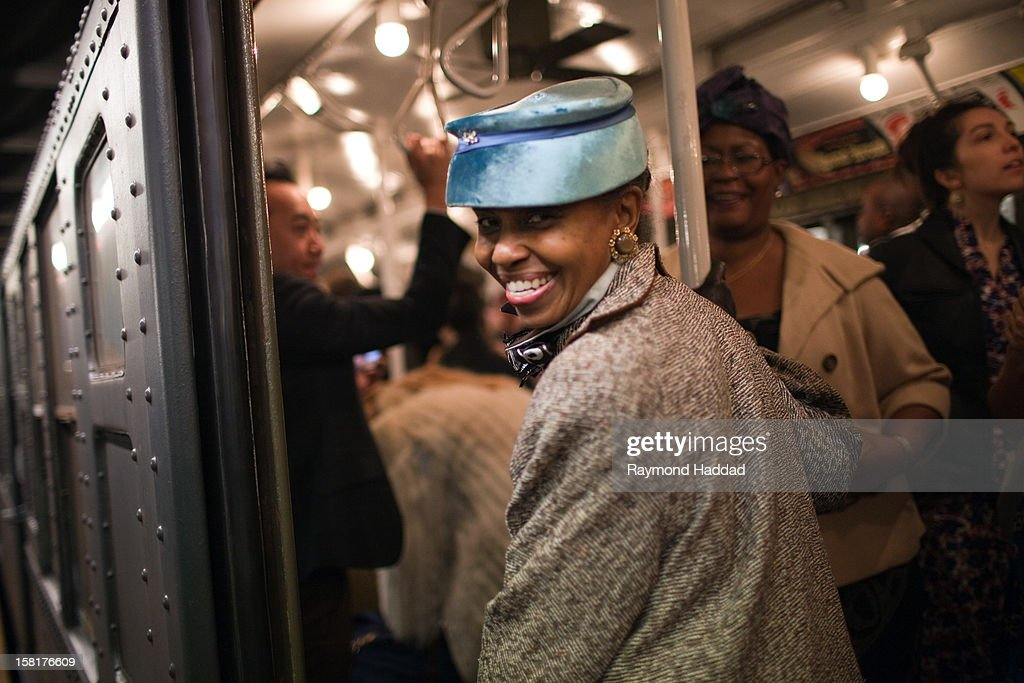 Jazz age vintage NYC subway train swing dance party 2011. African-American woman and passengers riding old vintage antique subway car in New York City.