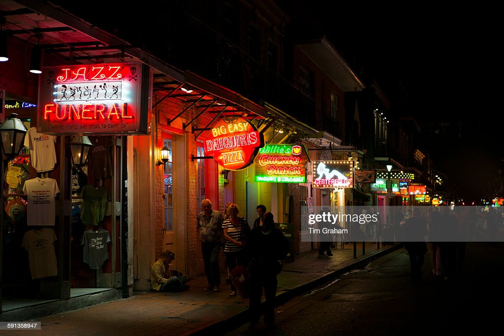 Jazz funeral daiquiris and pizza on offer among signs in famous Bourbon Street in French Quarter of New Orleans USA