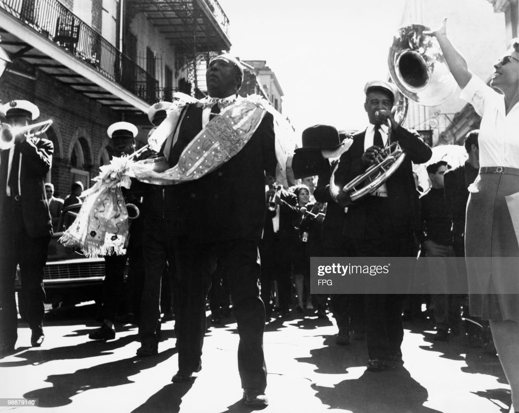 A jazz funeral procession for a deceased musician in New Orleans, Louisiana, circa 1965. The marching band traditionally plays slow dirges on the journey to the cemetery and upbeat melodies on the way back.