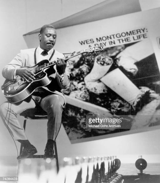 Jazz guitarist Wes Montgomery performs onstage in front of an enlarged cover of his album 'A Day In The Life' which was released in 1967